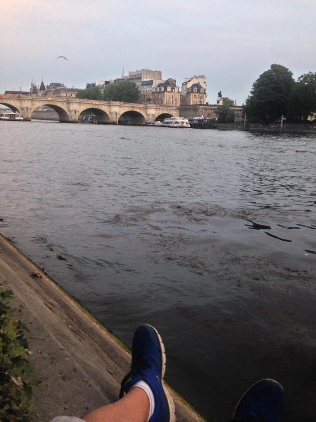 Sitting alone on the banks of the Seine River in Paris